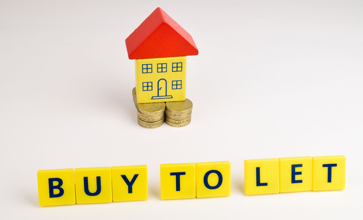 A toy house sitting on a stack of coins with the words, 'Buy To Let' in front of it.